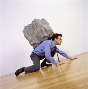 Man crouching with rock on his back